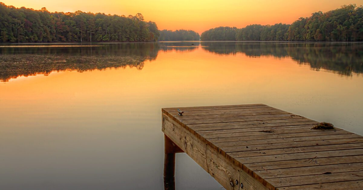 Sunrise on a calm fall morning at the Harwood's Mill Reservoir in York County, Virginia.